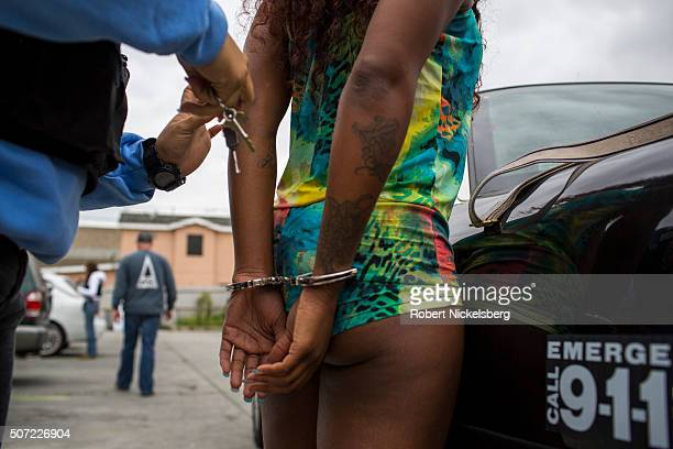 An unidentified Los Angeles police officer from the Human Trafficking Task Force hand cuffs an unidentified female suspect in a motel parking lot on...