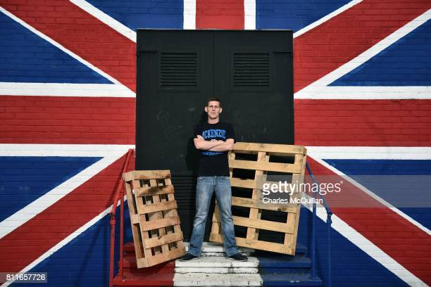 An unidentified Loyalist stands in front of a union jack mural at the Shankill road bonfire site on July 10 2017 in Belfast Northern Ireland The...