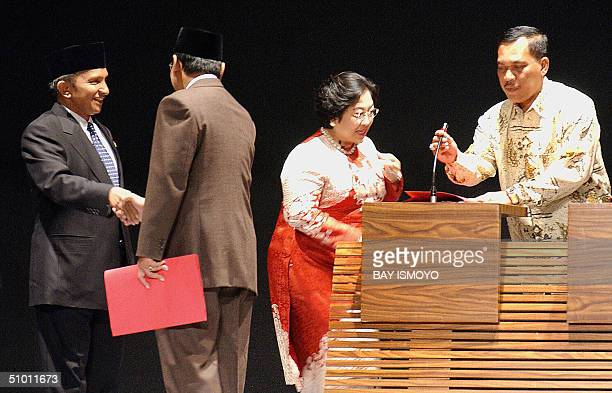 An unidentified man adjusts a microphone for candidate President Megawati Sukarnoputri as presidential candidate Amien Rais shakes hands with...