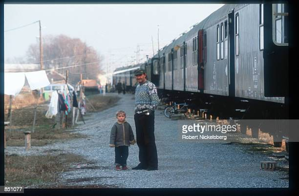 An unidentified man and a child stand near a train where many Croat and Muslim refugees live December 20 1994 in BosniaHerzegovina Civil war erupted...