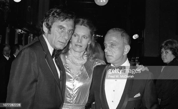 An unidentified man and woman pose with American attorney Roy Cohn at Cohn's birthday party at the Seventh Regiment Armory New York New York February...