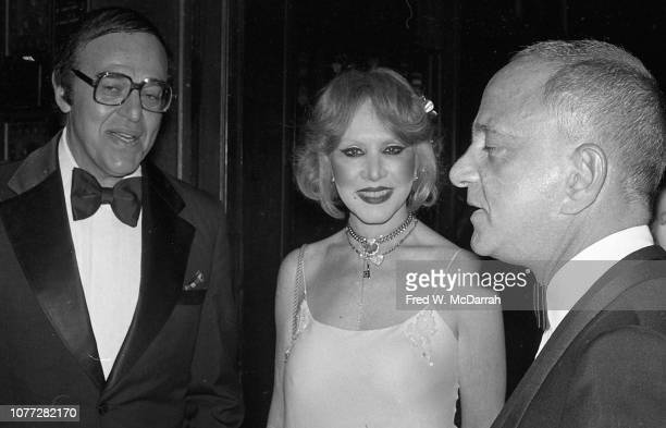 An unidentified man and woman speak with American attorney Roy Cohn at Cohn's birthday party at the Seventh Regiment Armory New York New York...