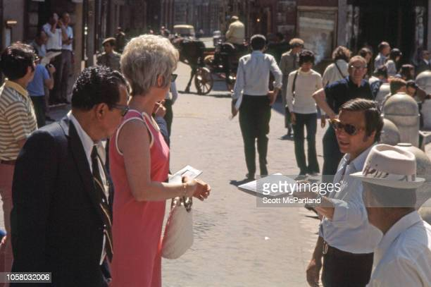 An unidentified man and woman stand on a street as a vendor offers them a travel guide book Siena Italy August 1968 In the background a man steers a...