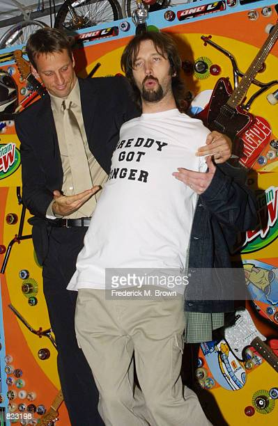 An unidentified man assists comedian Tom Green in removing his coat at the ESPN Action Sports Music Awards April 7 2001 in Los Angeles CA