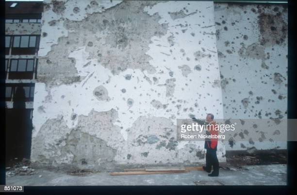 An unidentified man examines the destruction caused by the war December 19 1994 in BosniaHerzegovina Civil war erupted in Bosnia and Herzegovina...