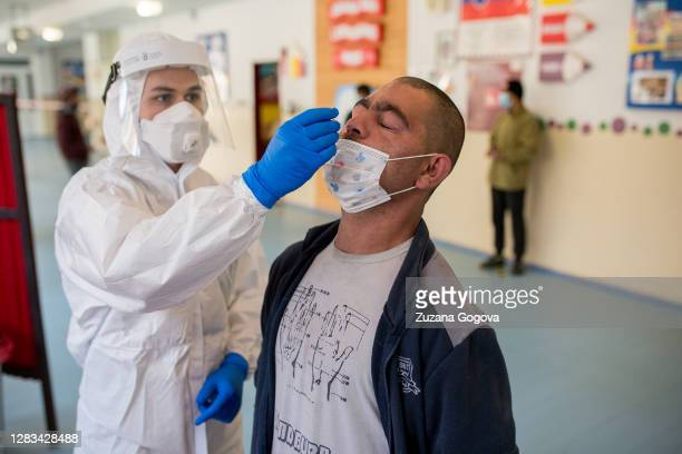 An unidentified man from Lunik IX borough is administered the antigen test for Covid-19 on November 1 in Kosice, Slovakia. Lunik IX houses the...