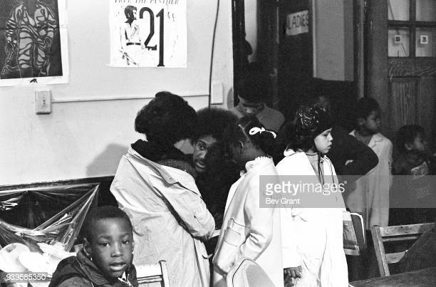 An unidentified man helped a group of kids with their coats during a free breakfast for children program sponsored by the Black Panther Party New...
