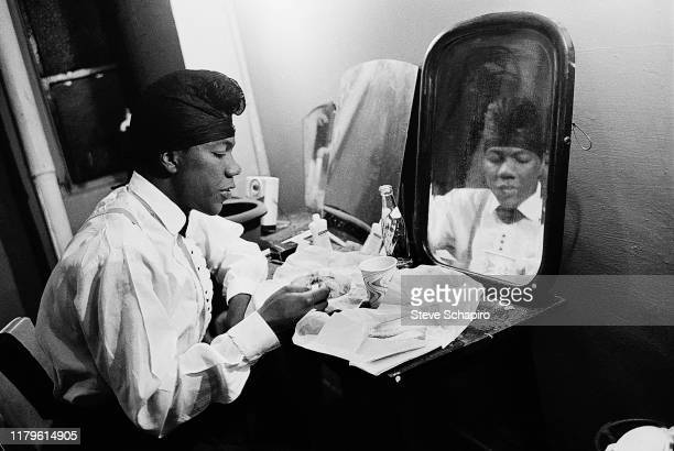 An unidentified man, his hair in a net, eats a meal as he sits backstage at the Apollo Theater, New York, New York, 1961.