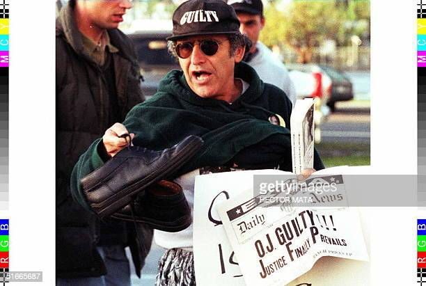 An unidentified man holding a fake newspaper and shoes protests against former US football star OJ Simpson near Santa Monica Court in Santa Monica CA...