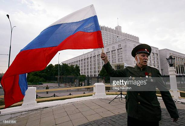 An unidentified man holds a Russian flag while on his way to a celebration of the 11th anniversary of the failed Communist coup attempt August 19...