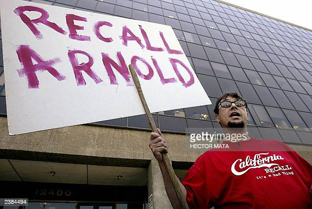 An unidentified man holds a sign as he demonstratse against the recall election near the entrance of the Los Angeles County Registrar's Office in...