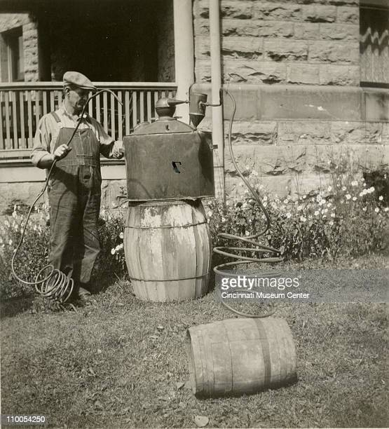 An unidentified man in overalls and a cap stands with a confiscated still outside a home Hillsboro Ohio 1928