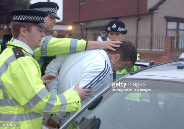 An unidentified man is led out of an address by police in Welling southeast London Tuesday October 11 2005 Five men including former asylum seekers...