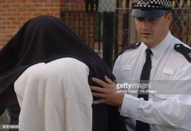 An unidentified man is led out of an address by police in Welling southeast London Tuesday October 11 2005 during raids to smash a multimillion pound...