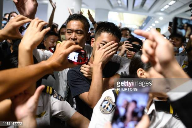 An unidentified man is shouted at by protesters during a demonstration at Hong Kong's International Airport on August 13 2019 Authorities at Hong...