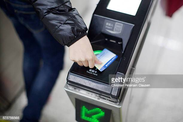 An unidentified man is using a contactless payment card at a gate at a Beijing subway station