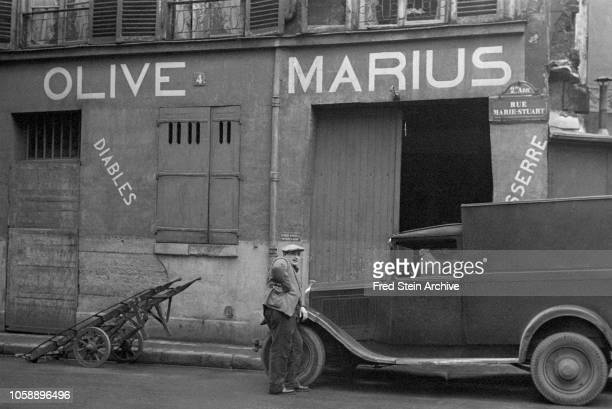 An unidentified man leans on the hood of a truck on Rue MarieStuart Paris France 1937 The building behind is painted with the words 'Olive Marius'...