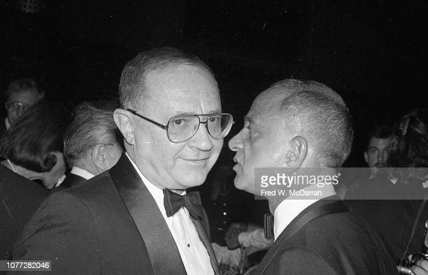 An unidentified man listens as American attorney Roy Cohn speaks into his ear at Cohn's birthday party at the Seventh Regiment Armory New York New...