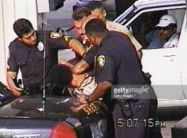 An unidentified man looks on as Inglewood police officers arrest 16yearold Donovan Jackson on July 8 2002 in Inglewood California Jackson was riding...