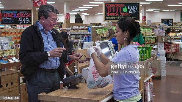 An unidentified man pays for groceries at Trader Joe's in Centreville Virginia on September 13 2013 The national supermarket chain informed parttime...