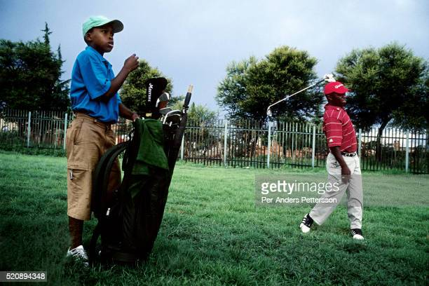 An unidentified man plays golf with a young boy as caddie at the Soweto Country Club in Soweto outside Johannesburg SA A growing number of people...