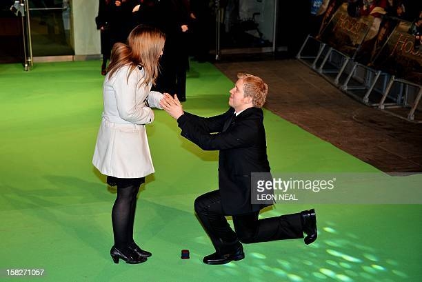 An unidentified man propses to his girlfriend on the Green Carpet at the European premiere of the first in the new trilogy of films based on the work...