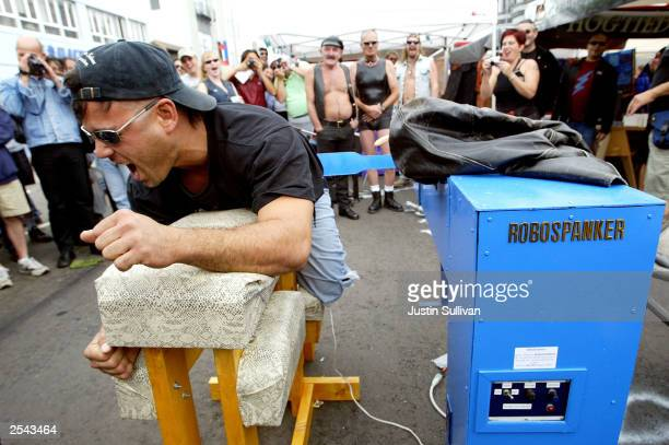 An unidentified man reacts after being spanked by the Robospanker spanking machine at the 20th Annual Folsom Street Fair September 28 2003 in San...