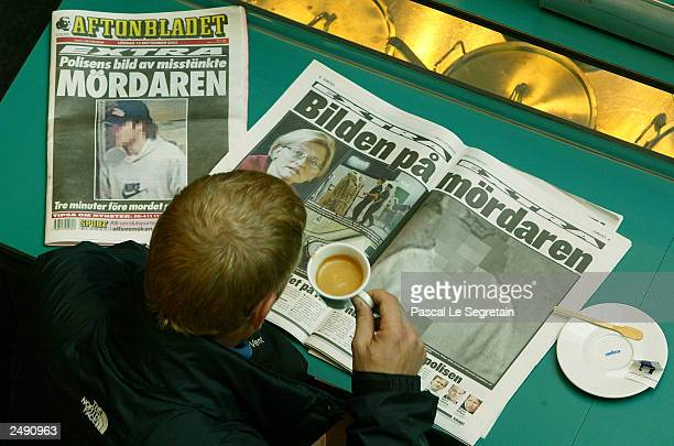 An unidentified man reads Swedish tabloid newspapers showing video surveillance images of a man police are searching for as a suspect in the murder...