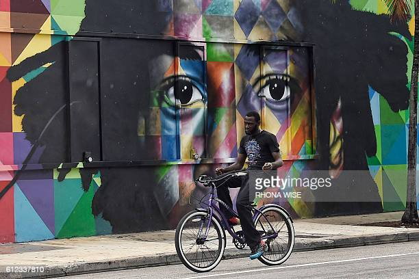 An unidentified man rides a bicycle in front of a mural by Brazilian artist Kobra in the Wynwood neighborhood of Miami Florida on September 28 2016...