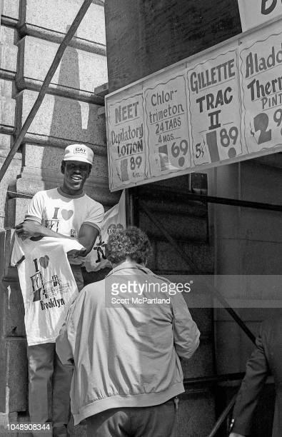 An unidentified man sells souvenir 'I Love Brooklyn' tshirts during the Brooklyn Bridge's 100th birthday celebrations in Brooklyn New York New York...