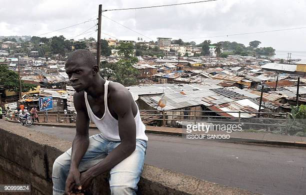 An unidentified man sits on a wall in a township in Freetown on September 20 2009 where Amnesty International SecretaryGeneral Irene Khan is...
