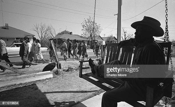 An unidentified man sits with one leg up on a porch swing as demonstrators in a voter registration march passes by Greenwood Mississippi 1964