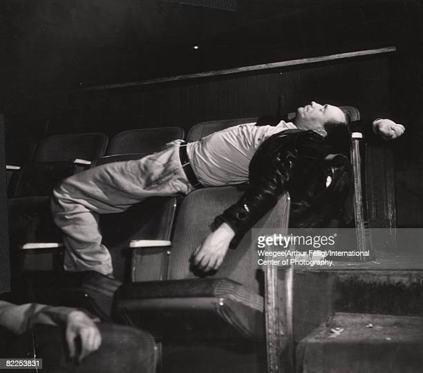 An unidentified man sleeps stretched across several seats in two rows at a movie theatre early 1940s Photo by Weegee/International Center of...