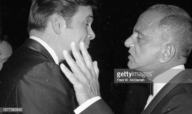 An unidentified man speaks with American attorney Roy Cohn at Cohn's birthday party at the Seventh Regiment Armory New York New York February 22 1981