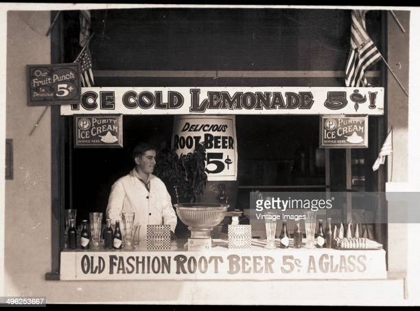 An unidentified man stands behind the counter of a stall that offers lemonade, root beer, Cracker Jacks, and ice cream for sale, 1920s or 1930s.