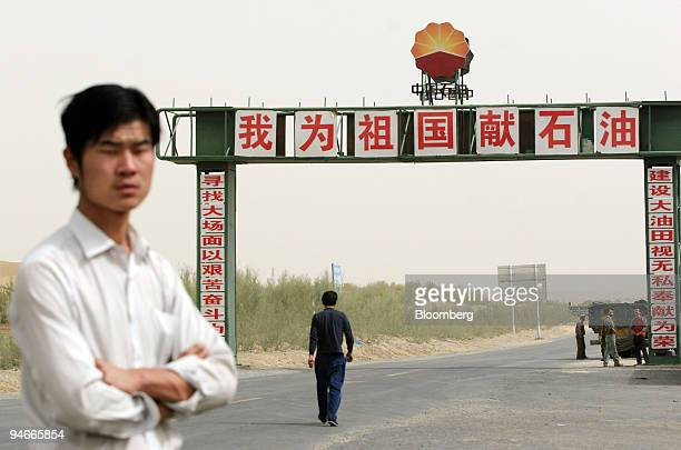 An unidentified man stands near a PetroChina gate reading 'The Chinese motherland offers petroleum' which greets visitors to the town of Tazhong...