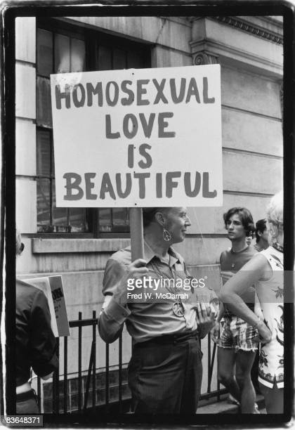 An unidentified man stands on a crowded sidewalk and holds a sign that reads 'Homosexual Love Is Beautiful Love' in anticipation of the second annual...