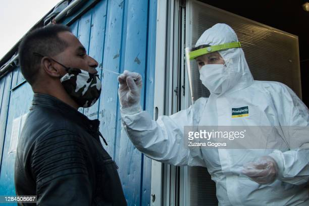 An unidentified man struggles to stay still while healthcare worker administrates the antigen test for Covid-19 on November 7, 2020 in Presov,...