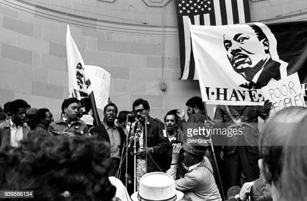 An unidentified man surrounded by others speaks into bank of microphones at Central Park's Naumburg Bandshell during the Poor People's Campaign 1968...