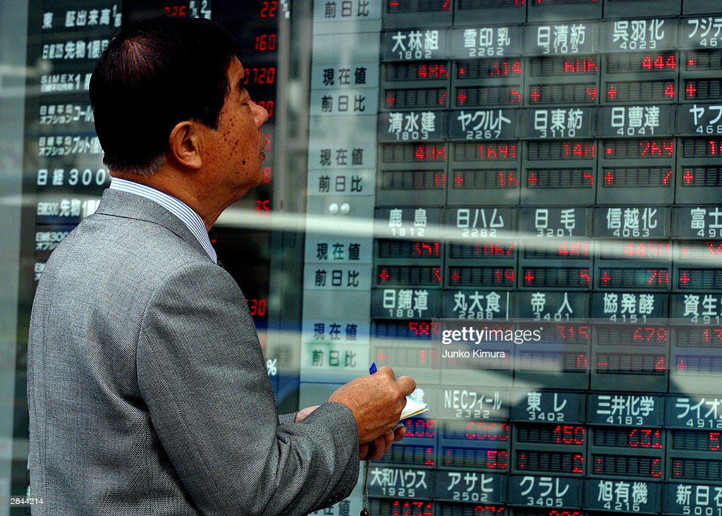 An unidentified man takes notes in front of the electric board flashing the share prices in a business district January 5, 2004 in Tokyo, Japan. The market opened after closing December 30, 2003 for the new year holiday. The nikkei stock average increased by 111.19 points, or approximately 1.04 percent and marked 10,787.83 points at the start of the trading.