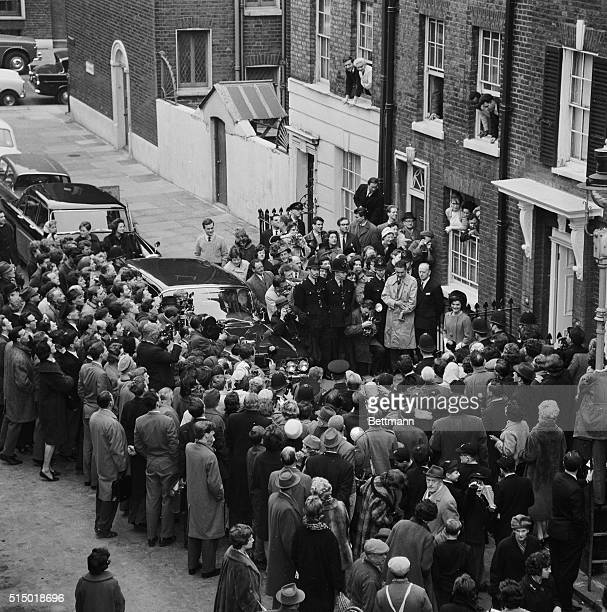 An unidentified man tries to calm crowd of newsmen photographers and admirers surging to greet Mrs Jacqueline Kennedy as she leaves the home of her...