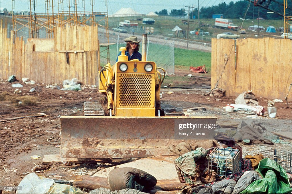 An unidentified man uses a bulldozer to clean the litter-filled grounds of the Woodstock Music and Arts Fair at the end of the festival, Bethel, New York, late August 1969. The festival ran from August 15 to 18.