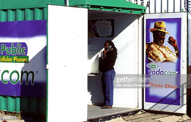 An unidentified man uses a phone in a container sponsored by Vodacom the British mobile phone telecom operator March 14 2001 in Khayelitsha a poor...