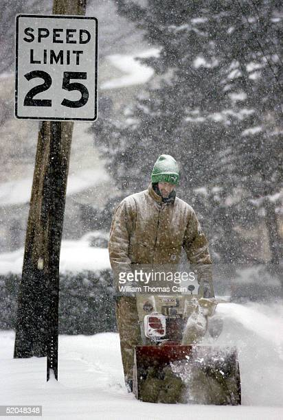 An unidentified man uses a snow blower to remove snow from the sidewalk near his home during a major winter snowstorm January 22 2005 in Warminster...