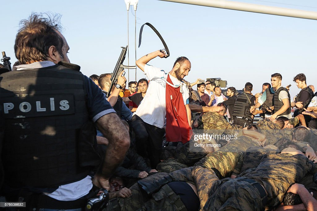 An unidentified man uses his belt to hit Turkish soldiers involved in the coup attempt that have now surrendered on Bosphorus bridge on July 16, 2016 in Istanbul, Turkey. Istanbul's bridges across the Bosphorus, the strait separating the European and Asian sides of the city, have been closed to traffic.Turkish President Recep Tayyip Erdogan has denounced an army coup attempt, that has left atleast 90 dead 1154 injured in overnight clashes in Istanbul and Ankara.