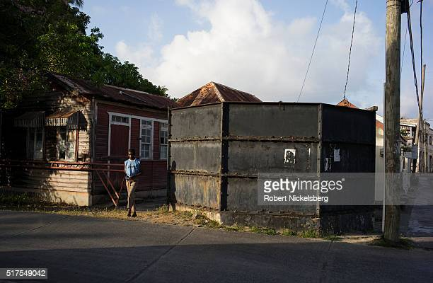 An unidentified man walks between woodensided house and a metal water tank Hillsborough Carriacou island Grenada March 3 2016
