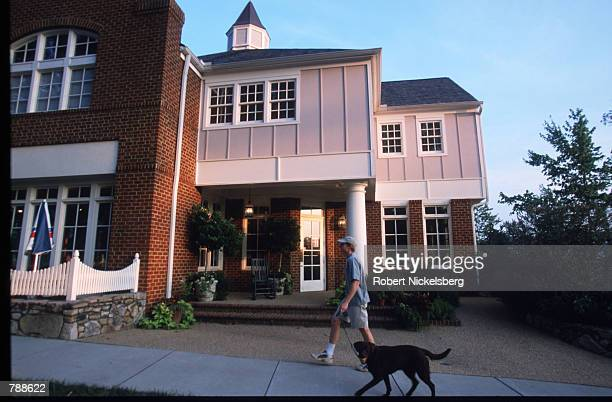 An unidentified man walks his dog in Southern Village August 1999 in Chapel Hill NC Southern village is a new suburb designed to resemble a small...
