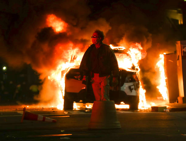 An unidentified man walks past a burning Boston Police car on Tremont Street in Boston on May 31, 2020 after a peaceful march from Dudley Square to...