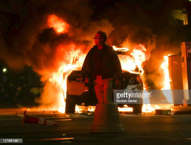 An unidentified man walks past a burning Boston Police car on Tremont Street in Boston on May 31 2020 after a peaceful march from Dudley Square to...
