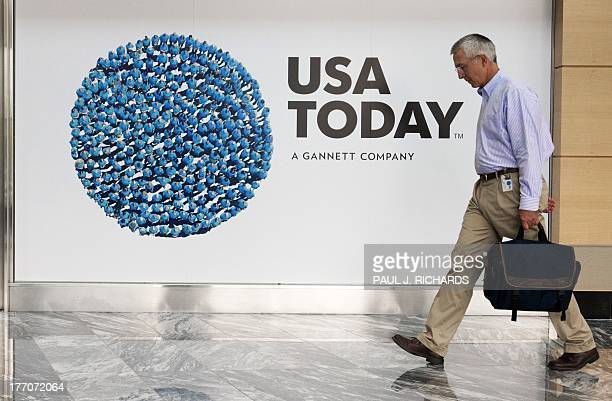 An unidentified man walks through the lobby of the GannettUSA Today headquarters building August 20 2013 on a 30acre site in McLean Virginia AFP...